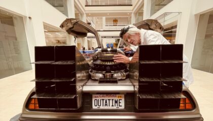'Doc' from back to the future inspects the delorian